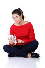 Student woman sitting cross-legged using a tablet