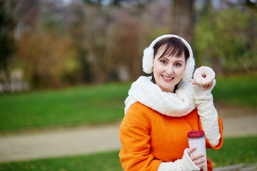 Cheerful young woman with donut