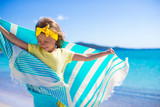 Fototapety Little adorable girl with beach towel during tropical vacation