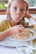 Adorable little girl eating spaghetti in outdoors restaraunt - 75910159