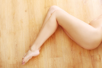Above view of nude female legs on the floor