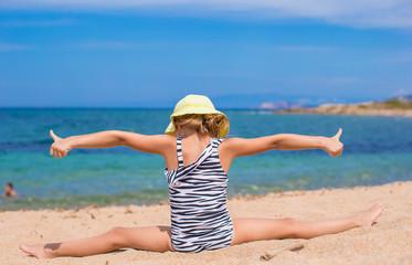 Adorable little girl making leg-split on tropical white sandy