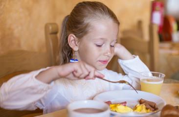 Adorable little girl having breakfast at indoor cafe