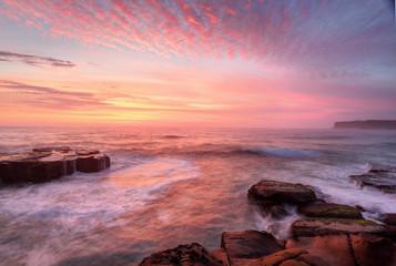 Sunrise skies and white water seas