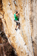 Young male rock climber on cliff