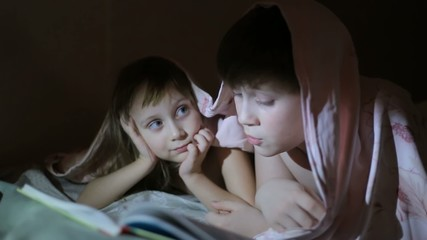 Boy reading a book to his sister lying under a sheet
