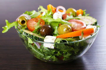 Greek salad in glass dish on wooden table background