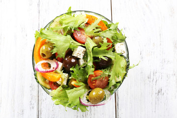 Greek salad in glass dish on color wooden table background