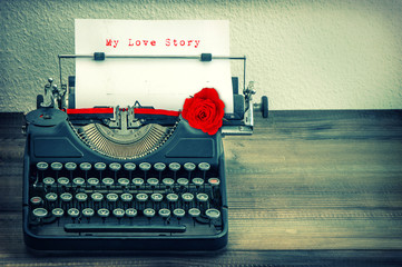 Vintage typewriter with white paper and red rose flower. Love St