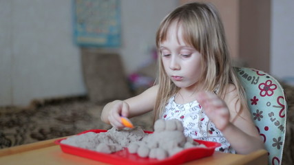 Little girl sculpts figures out of the kinetic sand, looking at