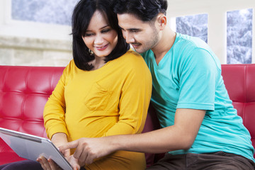 Attractive pregnant couple playing tablet