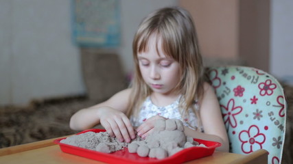 Little girl sculpts figures out of the kinetic sand, she does no