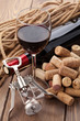 Glass of red wine, bottle, heap of corks and corkscrew