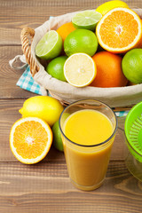 Citrus fruits in basket and glass of juice. Oranges, limes and l