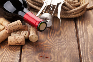 Red wine bottle, heap of corks and corkscrew