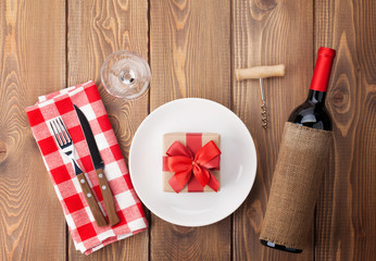Table setting with gift box on plate, wine glass and red wine bo