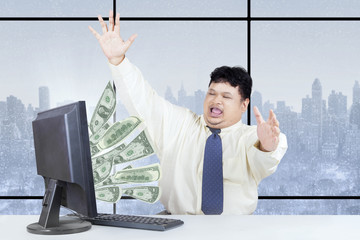 Excited businessman get money from internet