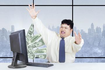 Excited businessman get money from internet