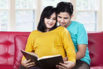 Expectant mother with her husband read book