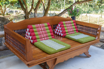 Wooden bed under tree