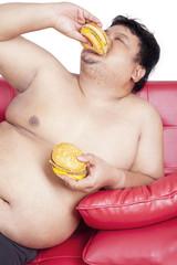 Expressive fat person eating burger