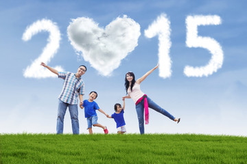 Family hold hands at field under cloud of 2015
