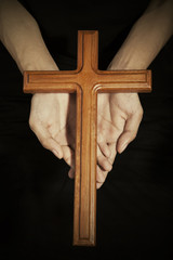 Hands with wooden cross on the palms