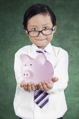 Little businessman showing piggybank 1