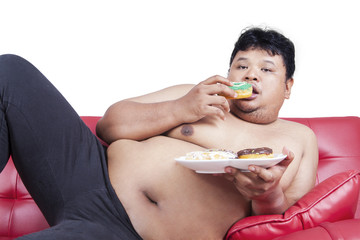 Obesity person eating donuts on sofa