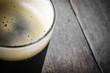 Leinwandbild Motiv Pint of Dark Beer on Wood Background