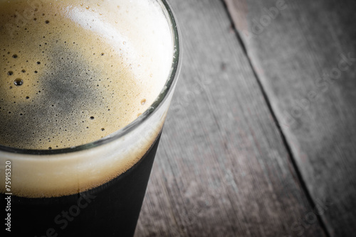 Fotobehang Bier Pint of Dark Beer on Wood Background