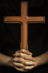 Wooden cross on the prayer hands
