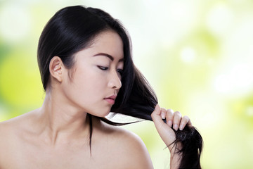 Young woman looking at her hair