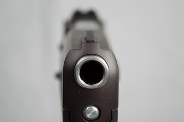 Closeup shot looking down the barrel and front sight of a pistol