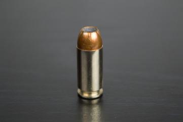 Single bullet for a gun on a black table