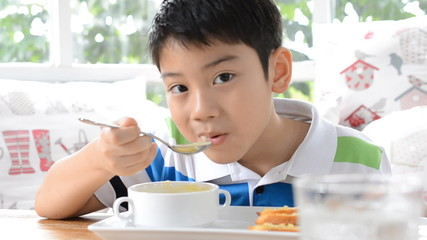 Asian cute child eating a soup