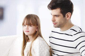 Portrait of cute girl and father sitting at sofa