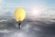 Businessman in glowing yellow lightbulb hot air balloon flying