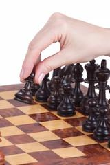 weibliche Hand haltet einen Bauern auf dem Schachbrett