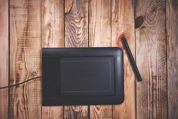 Графический планшет на деревянном фоне