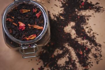 Чай в стеклянной баночке и заварка рассыпаная на фоне