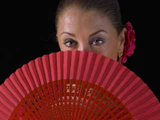 Closeup of a Flemish woman, from behind a hand fan