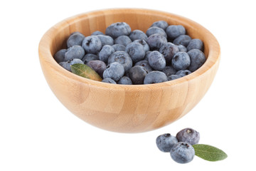 Wooden bowl with bilberry berries on a white background