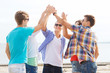 group of smiling friends making high five outdoors