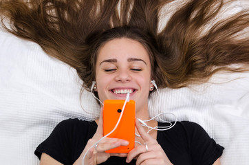 Teenager have fun with mobile laying on the bed