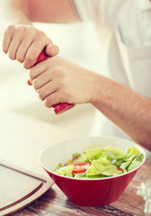 close up of male hands flavouring salad in a bowl