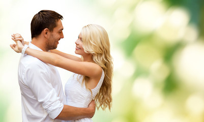 happy couple hugging over green background