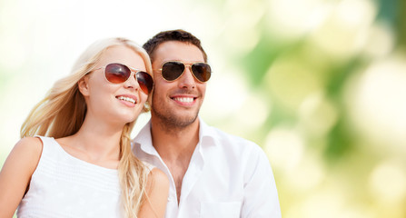 happy couple in shades over green background