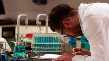 Scientist taking notes on his experiment