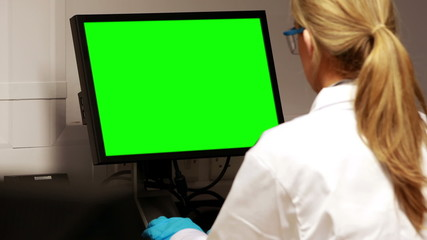 Scientist using computer with chroma key screen